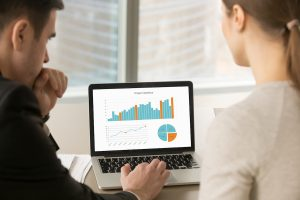 Businessman and Businesswoman Looking At Data Visualization - Rocket-Hire